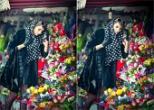 Beautiful brunette woman with gloves choosing flowers at the florist shop. Fashionable female