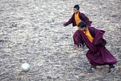 Two Young Buddhist Monk Playing Soccer