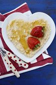 Plate Of Nutritious And Healthy Cooked Breakfast Oats With Strawberries And Honey In Heart Shaped Bo