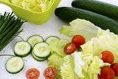 Salad Preparation With Cucumbers, Lettuce, Cherry Tomatoes And Chives On Modern White Wood Table Set
