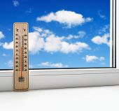 Thermometer On The Windowsill On A Background Of Clouds