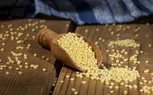 image of millet  - Millet in a wooden spoon on a wooden background - JPG