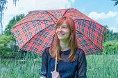 Girl under umbrella with rain in nature