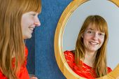 Portrait of redhead girl looking in mirror