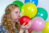 Girl blowing inflating colored balloons