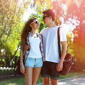 Sunny Portrait Of Happy Young Couple Teenagers In Urban Style Outdoors, Boyfriend Embracing Girl In