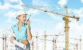 Woman in helmet, holding rolls of paper and talking on walkie-talkie. Tower cranes as backdrop