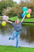 Girl holding up many balloons at pond
