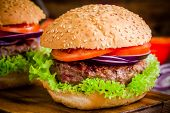 Homemade Hamburger With Fresh Green Lettuce, Tomato And Red Onion Closeup