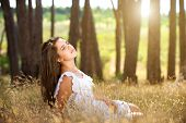 Dreamy Young Woman Sitting In Field With Sunlight In Background