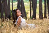 Beautiful Young Woman Sitting In A Field
