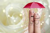 Conceptual finger art. Lovers is embracing and holding umbrella with falling flowers. Stock Image