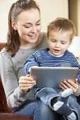Mother And Son Playing On Digital Tablet Together