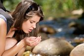 Young Woman Drinking Fresh Water From Stream In Nature