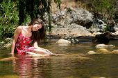 Happy Girl Sitting In Water With Red Dress