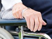 image of wheelchair  - Hands of an elderly woman resting on the wheelchair - JPG