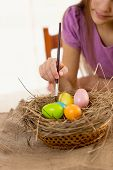 Girl Holding Paintbrush And Coloring Easter Eggs