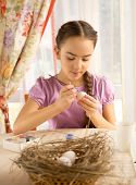 Young Girl Painting White Egg For Easter