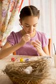 Concentrated Girl Painting Easter Eggs At Table