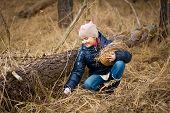 Girl Reaching For Easter Egg Under Log In Forest