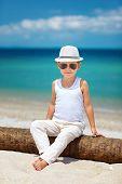 Stylish Kid Boy Sitting On Palm Tree At The Beach