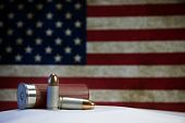 stock photo of 9mm  - Two 9mm bullets and a shotgun shell in front of an American flag.