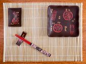 Bamboo mat, plates and chopstick on the table