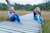 Two girls operating mobile phones on path in nature