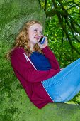 Girl calling with mobile phone in tree