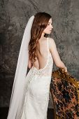 Back view of the beautiful woman posing in a elegant wedding dress