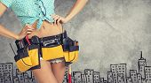 Woman in tool belt, hands on hips. Cropped image. Sketch buildings as backdrop
