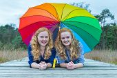 Two girls lying in nature under colorful umbrella