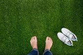 Feet Resting On Green Grass With Sneakers