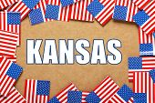 pic of kansas  - Miniature flags of the United States of America form a border on brown card around the name of the state of Kansas - JPG