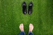 Feet Resting On Green Grass With Standing Opposite Boots