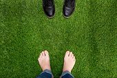 Mens Feet Resting On Green Grass With Standing Opposite Boots