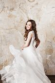 Beautiful smiling bride with perfect makeup and hair style in elegant wedding dress