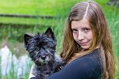 Girl carrying black dog on arm in park