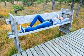 Teenage girl lying on bench in forest