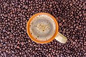 orange cup of drink coffee on a heap of roasted coffee beans