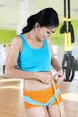 Fitness Woman Using Measuring Tape