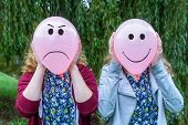 foto of incognito  - Two teenage girls holding balloons with happy and angry facial expressions - JPG