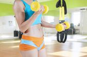Woman Trains Arms Muscle With Two Dumbbells