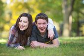 stock photo of bff  - Smiling male and female teen friends relaxing outdoors - JPG