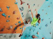 stock photo of climbing wall  - Beautiful sporty young woman climbing on practical wall in gym bouldering - JPG