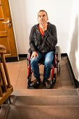 picture of disability  - a disabled man in a wheelchair is facing a barrier of stairs - JPG