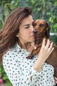 foto of dachshund dog  - A Attractive woman playing with dachshund dog - JPG