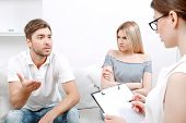 picture of psychologist  - Young man explaining his problems to doctor and his girlfriend sitting next offended crossing arms angrily - JPG