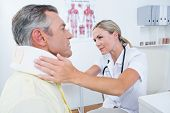 pic of neck brace  - Doctor examining patient wearing neck brace in medical office - JPG