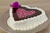 stock photo of icing  - Valentine Chocolate icing cake with flower and hearts - JPG